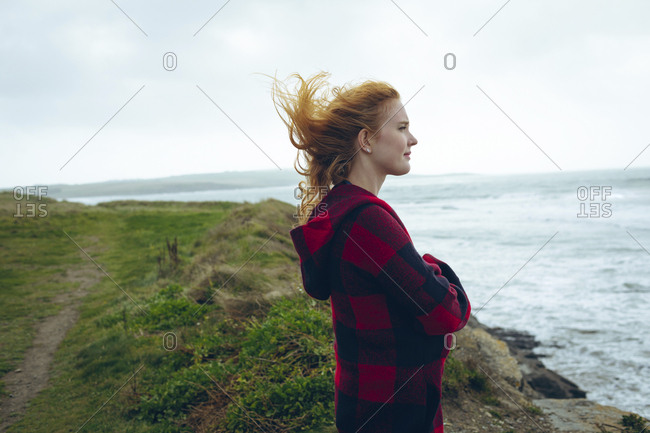 Thoughtful redhead woman standing with arms crossed in the beach