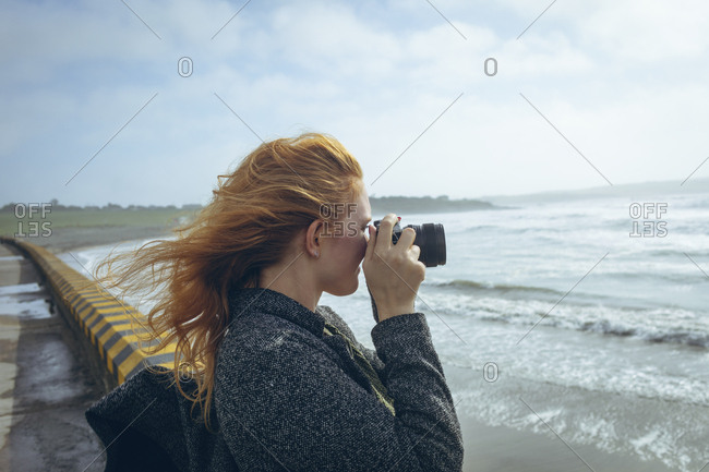 Redhead woman clicking photo with camera in the beach