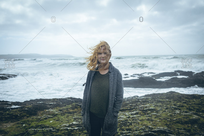 Redhead woman standing with hands in pocket at beach