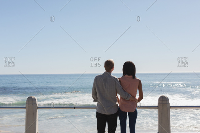 Rear view of couple standing together near railing at beach