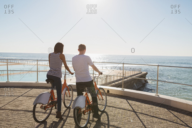 Couple with bicycle standing on promenade near beach