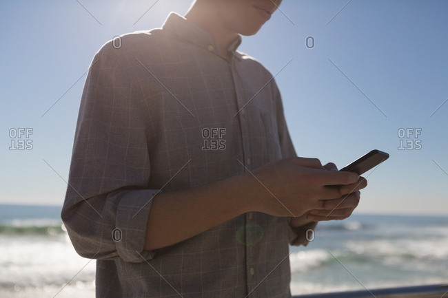 Mid section of man using mobile phone near beach