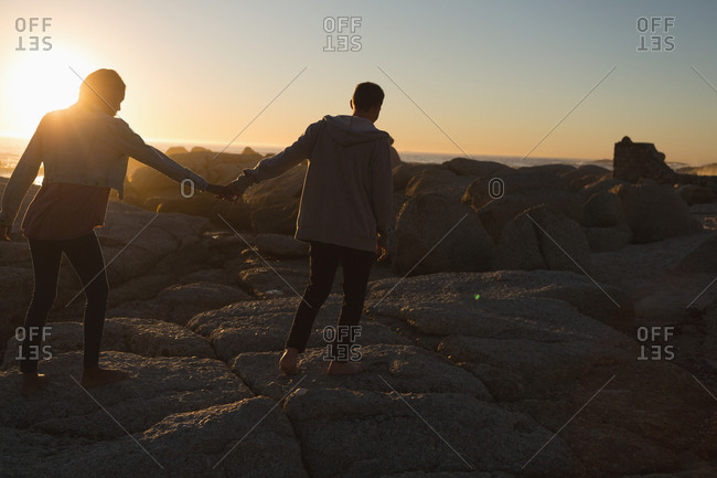 Rear view of couple holding hands walking on beach