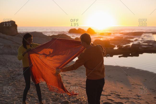 Couple having fun on beach during sunset