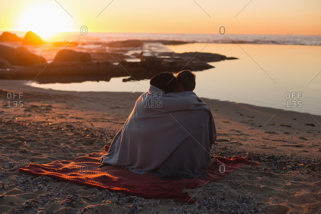 Couple romancing on beach during sunset