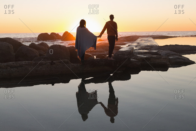 Rear view of couple holding hand standing on beach during sunset