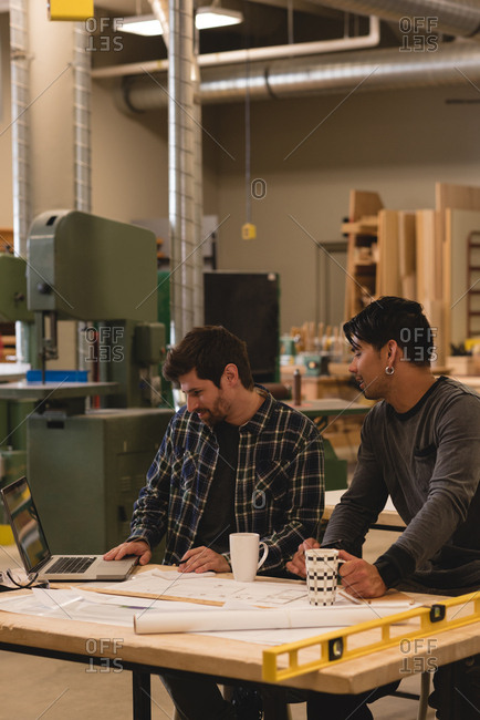 Two attentive craftsman using laptop in workshop