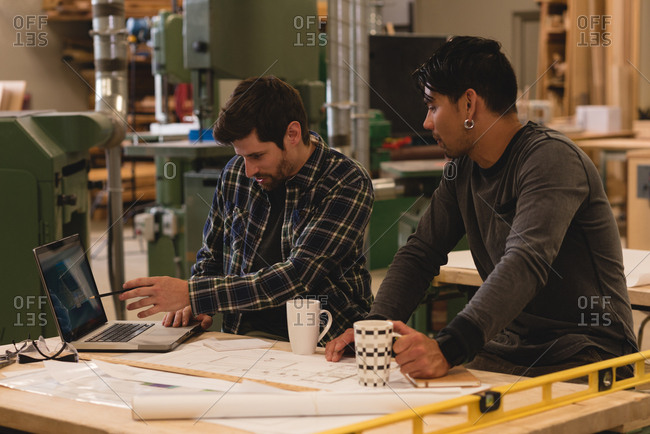 Two attentive craftsman discussing over laptop in workshop
