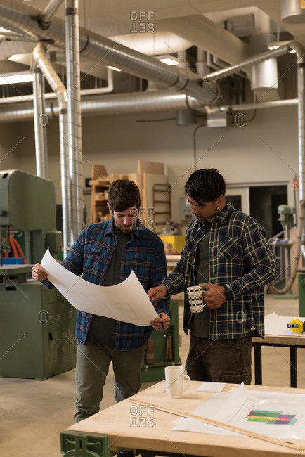 Two craftsman discussing over a blueprint in workshop
