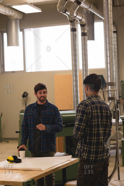 Two craftsman interacting with each other in workshop