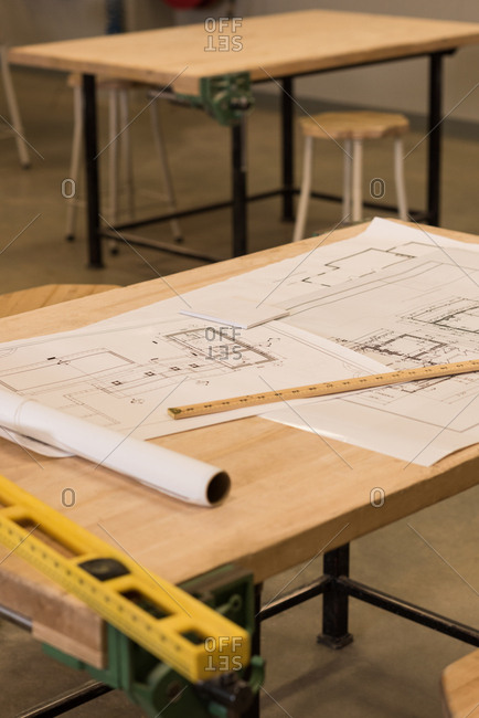 Blueprint and instrument on table in workshop