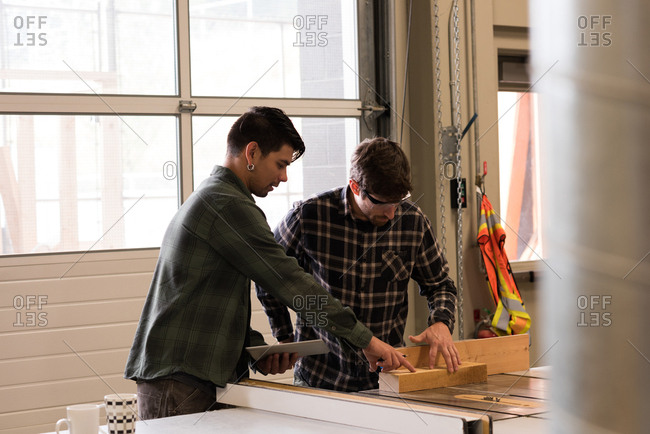 Two craftsman discussing over wooden plank in workshop