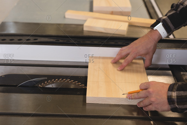 Close-up of craftsman measuring wooden plank in workshop