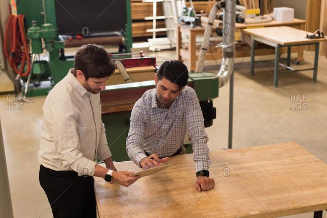 Two craftsman discussing over digital tablet in workshop