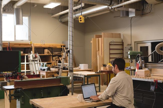 Rear view of craftsman using laptop in workshop