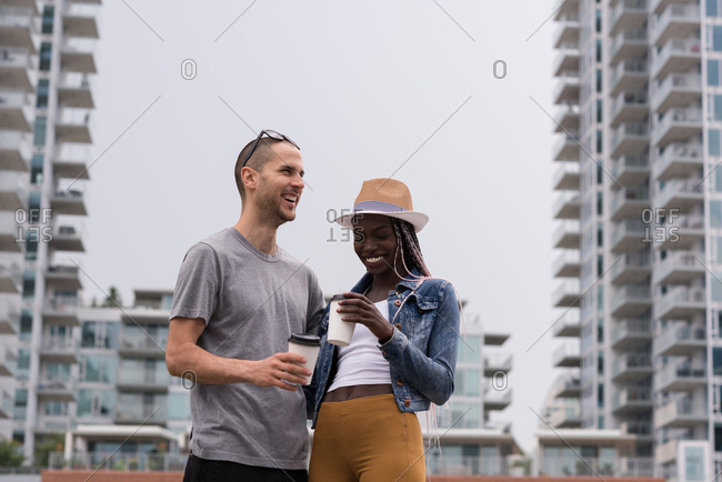 Happy young couple with coffee cup standing against the city buildings