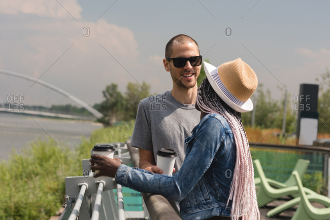Smiling couple with coffee cup standing near the railings