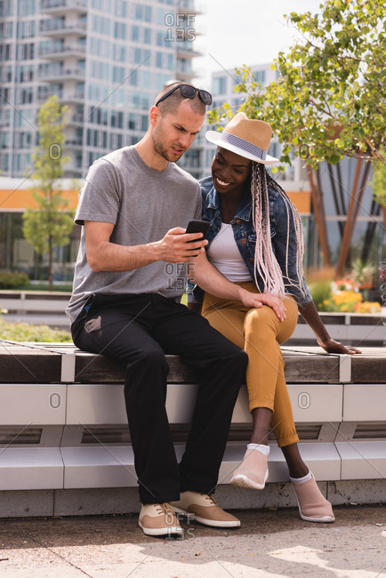 Smiling couple sitting on the bench and using mobile phone in city