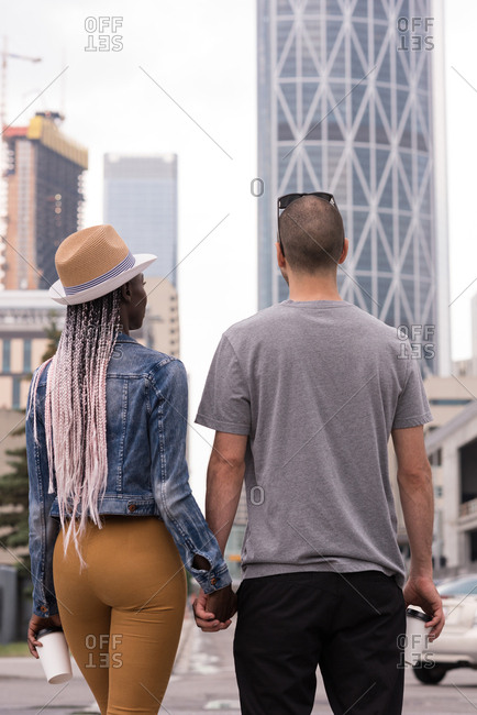 Rear view of couple holding hands crossing the street in city