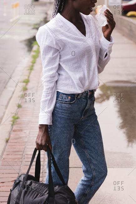 Young woman with a handbag eating burger on the sidewalk