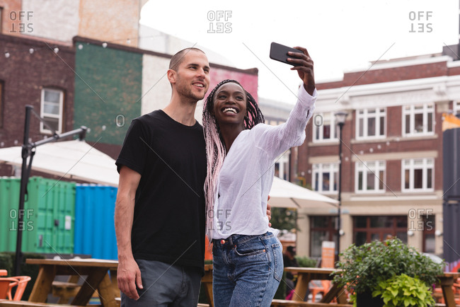Smiling young couple taking a selfie against the buildings