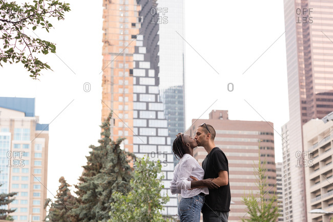 Romantic young couple kissing in the city against the buildings