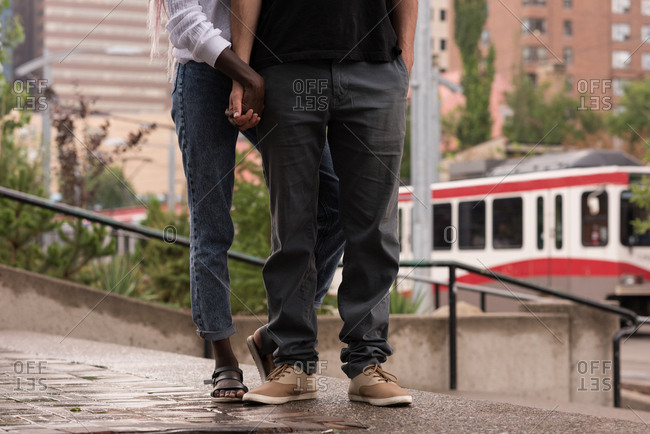 Close-up of couple standing on the pavement in city