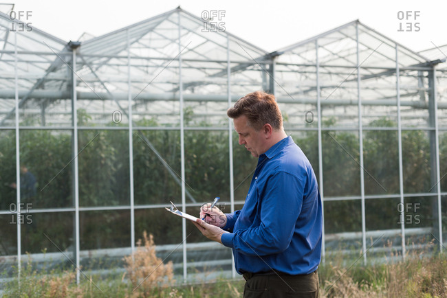 Concentrated man writing on clipboard in greenhouse