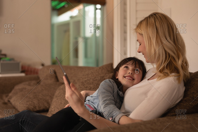 Mother and daughter using digital tablet in living room at home
