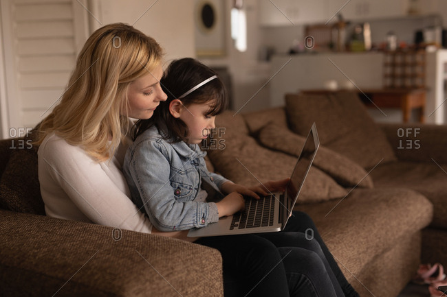 Mother and daughter using laptop in living room at home