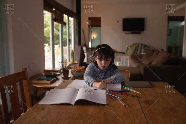 Innocent girl doing her homework at home
