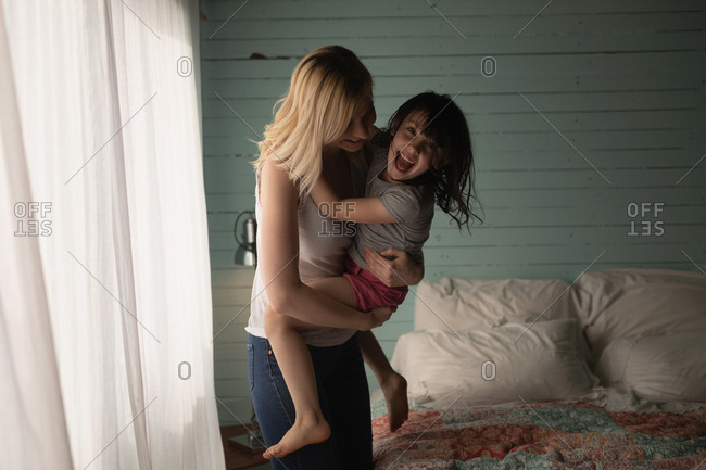 Mother and daughter embracing each other in bedroom at home