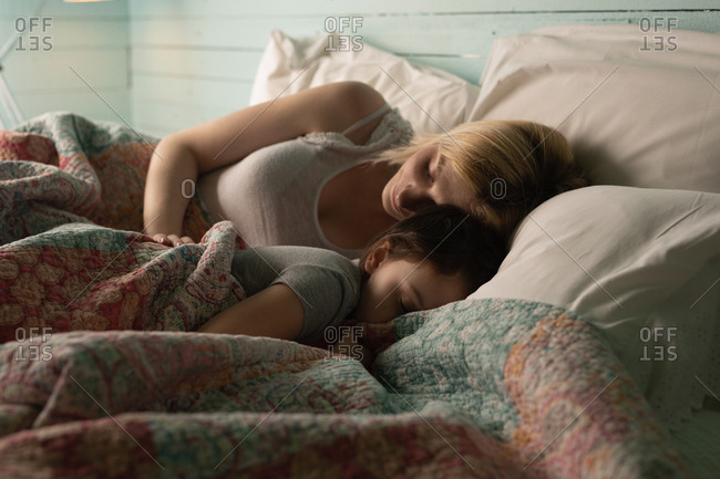 Mother and daughter sleeping in bedroom at home