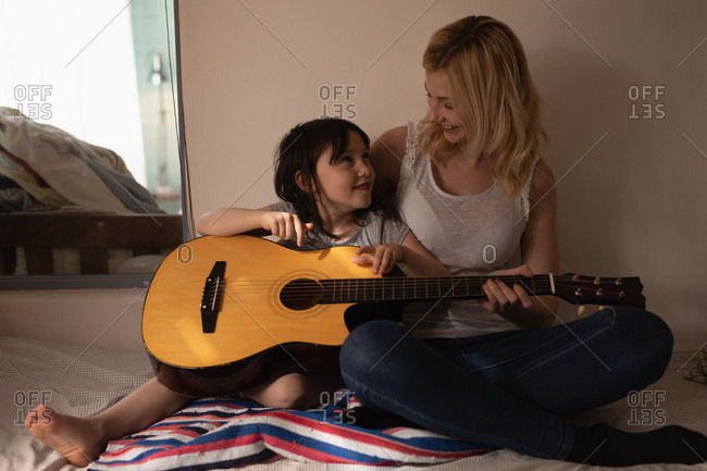 Mother and daughter playing guitar in bedroom at home