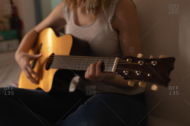 Mid section of woman playing guitar in bedroom at home