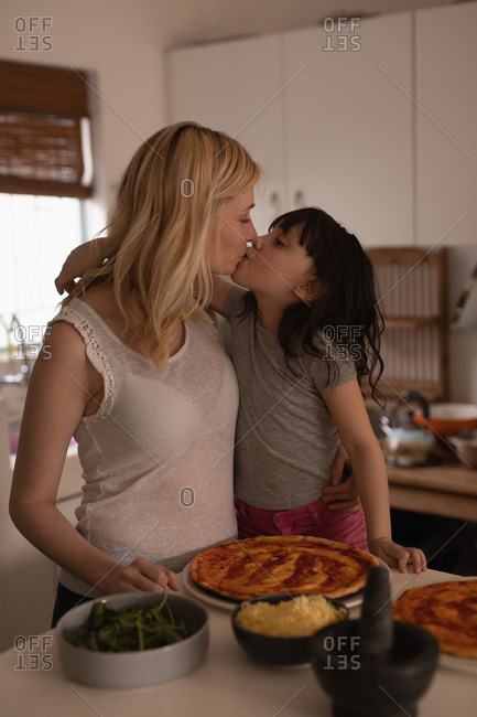 Mother kissing her daughter while preparing food in kitchen at home