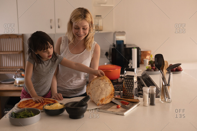 Mother and daughter preparing food in kitchen at home