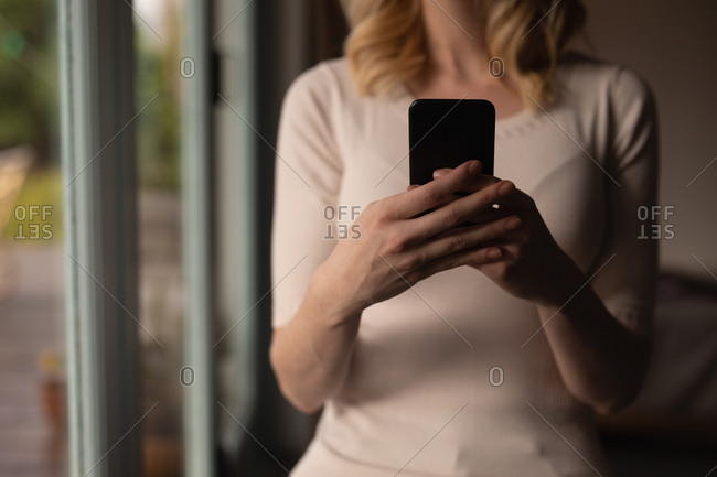 Mid section of woman using mobile phone at home