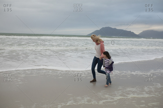 Mother and daughter walking together hand in hand at beach