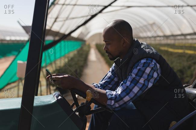 Man using mobile phone while sitting on tractor at blueberry farm