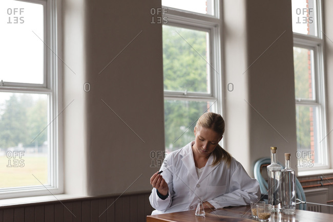 Female worker checking quality of gin in factory