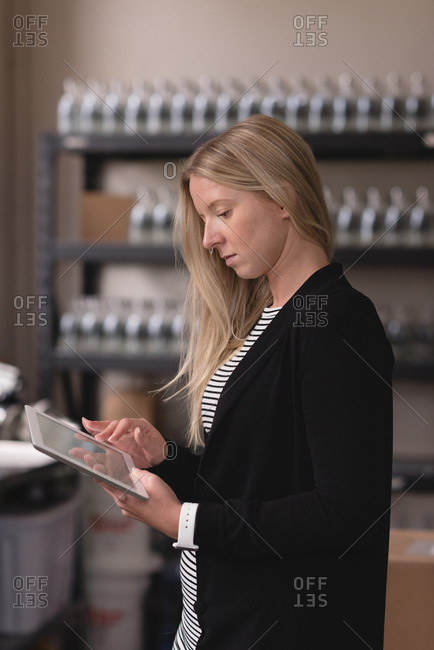 Beautiful female worker using digital tablet in factory