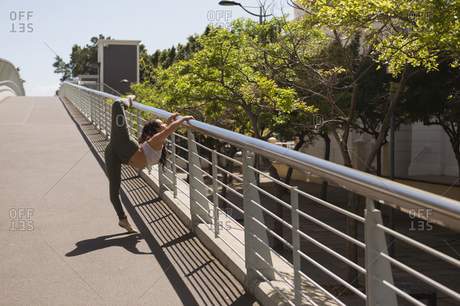 Side view of urban dancer practicing dance on bridge railing