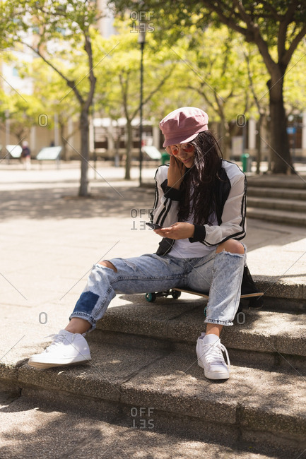 Young female skateboarder using mobile phone in city