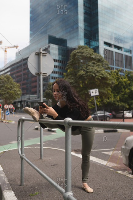Urban dancer using mobile phone while practicing dance in the city