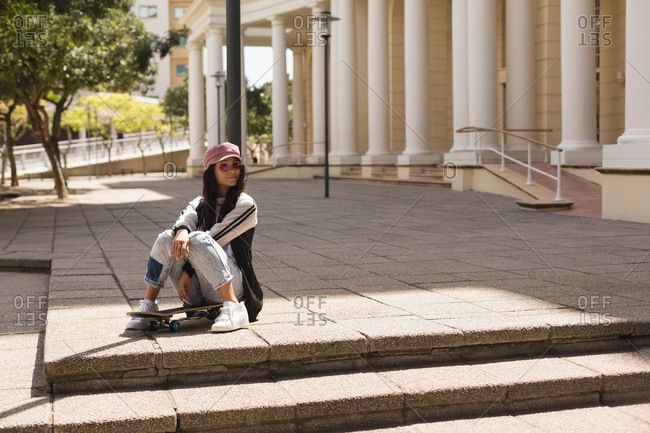 Female skateboarder sitting on skateboard in the city
