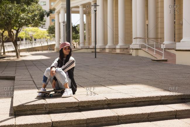 Female skateboarder sitting on skateboard in the city