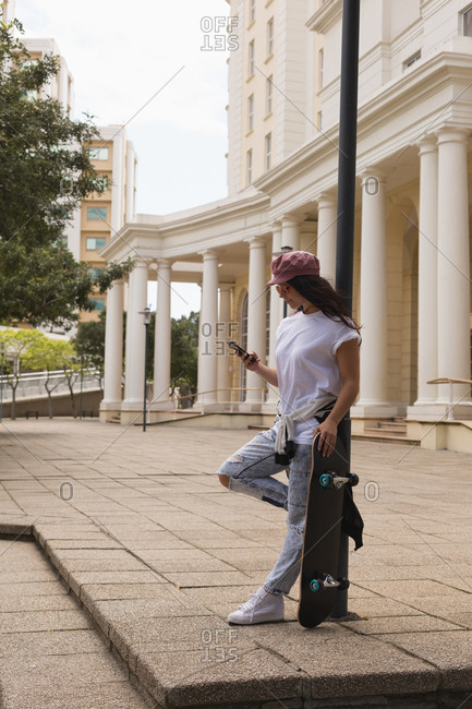Side view of female skateboarder using mobile phone in city