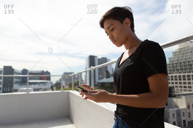 Side view of model using mobile phone on terrace