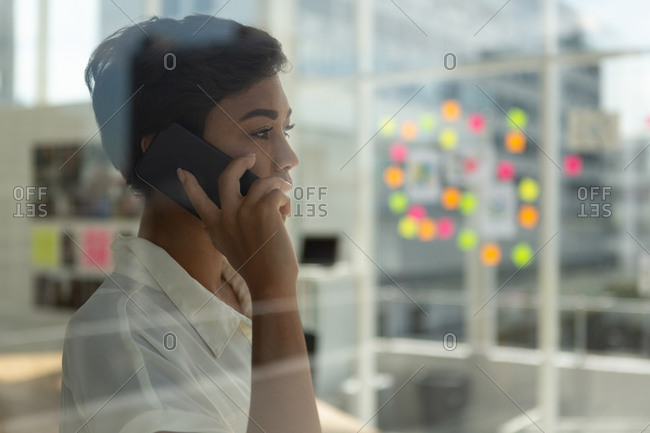 Side view of business executive talking on mobile phone in office